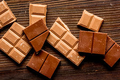 Black and milk chocolate pieces wooden table background top view Royalty Free Stock Image