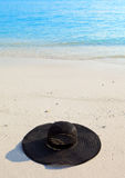 Black millinery  from sun ays on sand before ocean Royalty Free Stock Photo