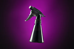 Black mini spray bottle isolated on purple and black Royalty Free Stock Photography