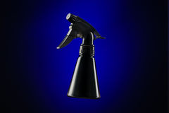 Black mini spray bottle over blue background Stock Photo
