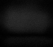 Black minimalist grainy wall background and black floor. Royalty Free Stock Image