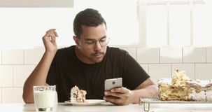 Black mixed race man with a smartphone has a breakfast with cake and milk. In sunny loft space stock video footage