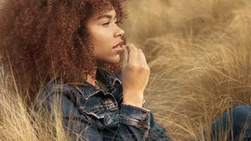 Black mixed race woman with big afro curly hair in lawn field with high dry autumn hay grass and sunset light. Black mixed race woman with big afro curly hair stock video