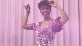 Black mixed race woman with short haircut and curly natural hair wears sequin sparkly dress in pink