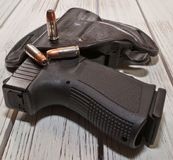 A holstered black pistol with several bullets on a wooden table. A black 9mm pistol in a holster on a wooden table, three hollow point bullets are on the top of Stock Photography