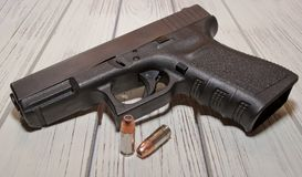 A black pistol with bullets on a wooden table. A black 9mm pistol with two hollow point bullets in front of it on a wooden table Stock Photos