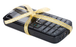 Black mobile phone with gold ribbon Royalty Free Stock Photography