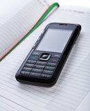 Black Mobile Phone On A Notepad Royalty Free Stock Photography