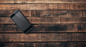 Black mobile phone on a wooden table Royalty Free Stock Photos