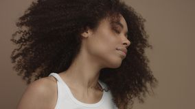 Black model with huge curly hair moving shaking hair in slow motion from 60 fps