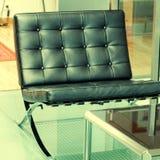 Black modern armchair on glass floor Stock Photos