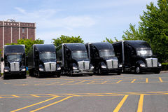 Black modern big rigs semi trucks on parking lot in row Royalty Free Stock Photo