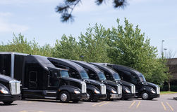 Black modern big rigs semi trucks in row on the parking lot. Powerful stylish black big rig semi trucks with black semi trailers are lined up in an open parking Royalty Free Stock Photography
