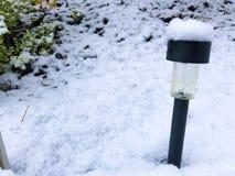 Black modern Garden Solar energie lamp under the snow stock images