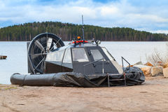 Black modern hovercraft is laying on the coast Royalty Free Stock Image