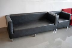 Black modern leather sofa in resting area. Of office building Royalty Free Stock Images