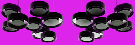 Black modern metal lamps hanging from a purple ceiling Royalty Free Stock Photos