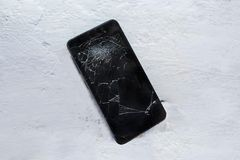 Modern broken mobile phone. Black Modern phone fell on the concrete floor and shattered the screen.. Copy space. Top view stock photo