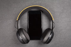 Black modern smartphone and headphones Royalty Free Stock Images