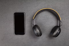 Black modern smartphone and headphones Royalty Free Stock Photos