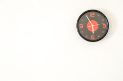 Black modern wall clock on white concrete wall with palce for te Stock Photos