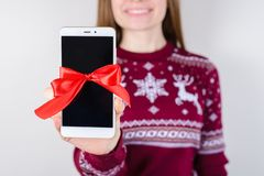 Black monitor perfect surprise concept! Cropped close up photo o. F happy smiling woman showing cell phone to camera isolated on grey background stock photo
