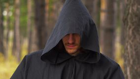 Ghost in the woods. The black monk walks between the trees in the forest stock footage