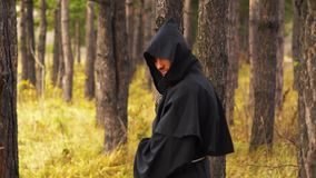 Ghost in the woods. The black monk walks between the trees in the forest stock video