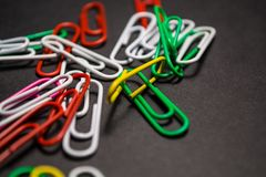 On black monophonic background plastic multi-colored paper clips   are lie. White, red, green, yellow colors. Office. On black monophonic background plastic royalty free stock photos