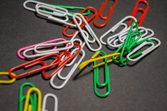 On black monophonic background plastic multi-colored paper clips   are lie. White, red, green, yellow colors. Office. On black monophonic background plastic stock image