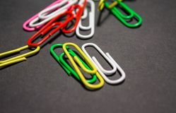 On black monophonic background plastic multi-colored paper clips   are lie. White, red, green, yellow colors. Office. On black monophonic background plastic stock images