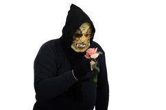 Black monster smelling a pink rose. Black masked monster smelling a pink rose on white background Stock Photo