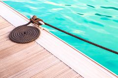 Black mooring rope arrange in circle on wooden pier with blue wa Stock Photo