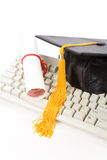 Black Mortarboard and computer keyboard. Online learning Royalty Free Stock Photo