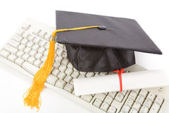 Black Mortarboard and computer keyboard. Online learning Royalty Free Stock Image