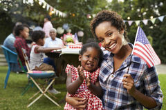 Black mother and baby hold flag at 4th July party, to camera Royalty Free Stock Images