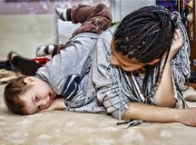 Dark-skinned Mom, Mom, plays, little son, son, boy, baby, on the stock images
