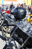 Black moto helmet on motorcycle handlebars. Against blurred background Stock Photos