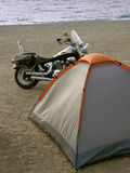 Black motorbike. And gray-orange tent on a sandy beach near the Adriatic sea. Vertical color photo Stock Images