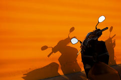 Black motorbike near an orange wall Royalty Free Stock Photos