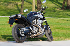 Black Motorcycle. Parked in the green field Stock Image