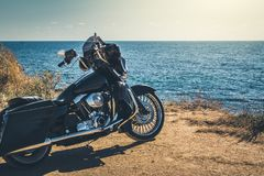 Black motorcycle on beautiful seacoast and blue sky onward. Prairie, steppe, summer. stock photos