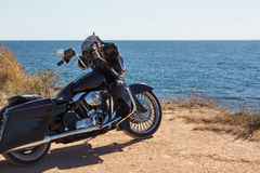 Black motorcycle on beautiful seacoast and blue sky onward. Prairie, steppe, summer. Royalty Free Stock Images