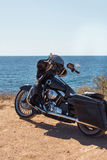 Black motorcycle on beautiful seacoast and blue sky. Prairie, steppe, summer. Stock Photos