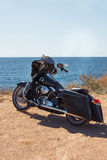 Black motorcycle on beautiful seacoast and blue sky. Prairie, steppe, summer. Stock Image