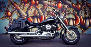 Black motorcycle and the graffiti wall Royalty Free Stock Photography