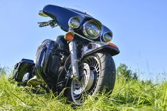 Black motorcycle Harley Davidson stands on the green grass. Bottom view royalty free stock photo