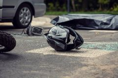 Black motorcycle helmet on the street after collision with a car. Concept photo stock photos