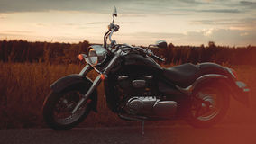 Black motorcycle on the roadside. Near the fields Royalty Free Stock Photography