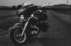 Black motorcycle on the roadside. Near the mountains Stock Photos